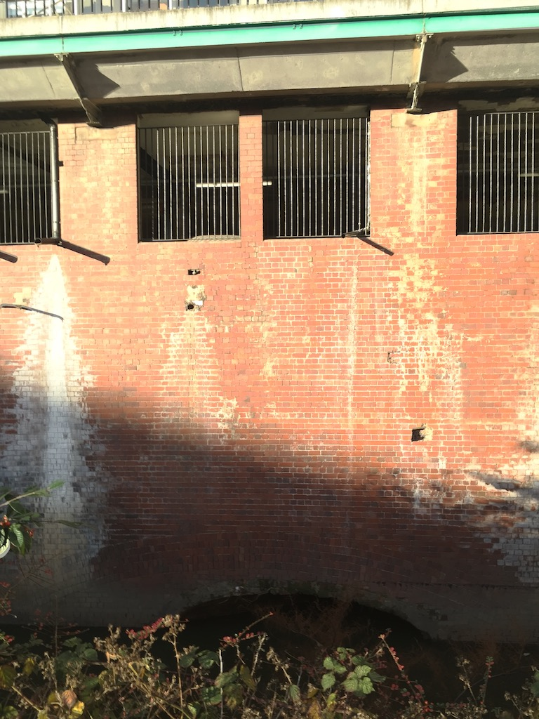 Photo of the visible entrance of the Duke's Tunnel on the River Medlock, from a car park off Hulme Street